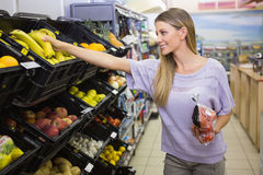 Smiling pretty blonde woman buying bananas Royalty Free Stock Image