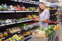 Smiling pretty blonde woman buying peppers Royalty Free Stock Images