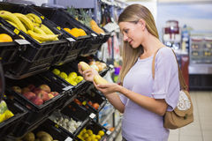Smiling pretty blonde woman buying potatoes Stock Photo