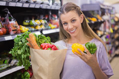 Smiling pretty blonde woman buying vegetables Royalty Free Stock Images