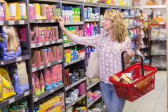 Smiling pretty blonde woman looking at shelf Stock Images