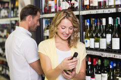 Smiling pretty blonde woman looking at wine bottle Royalty Free Stock Photo