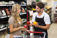 Smiling pretty blonde woman speaking with seller. Smiling pretty blonde women speaking with selle at supermarket Stock Photos