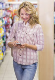 Smiling pretty blonde woman using her smartphone Stock Photos