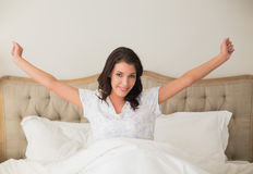 Smiling pretty brown haired woman stretching her arms Royalty Free Stock Photos