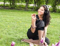 Smiling pretty  brunette sits on the grass Stock Image