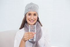 Smiling pretty brunette with winter hat on holding glass of water Royalty Free Stock Photography