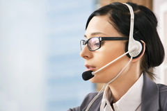 Smiling pretty business woman with headset Stock Photo