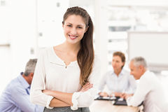 Smiling pretty businesswoman in front of colleagues Stock Photography