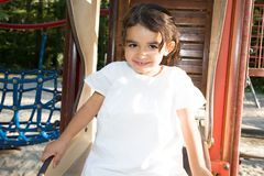 Pretty child girl in children playground park area in vacation day stock image