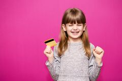 Free Smiling Pretty Child Girl With Hands Up In Winner Pose Holding Credit Card While Rejoices Over Purple Background Royalty Free Stock Images - 174640609