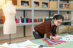 Smiling pretty designer woman holding blue zipper. Looking at sample design draw paper checking whether match and confirm color stock images