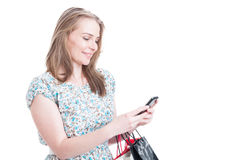 Smiling pretty female with shopping bags texting Royalty Free Stock Photo