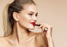 Smiling pretty girl applying red lipstick. Royalty Free Stock Images