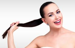 Smiling pretty girl with beautiful long dark brown hair. Grey background. Skin and hair care concept stock images