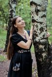 Smiling pretty girl in black Russian dress with embroidery leaned against birch royalty free stock photography