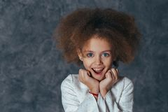 Smiling pretty girl with curly hair holds hands near face and is delighted stock images