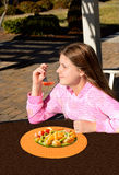 Smiling pretty girl eating healthy fruit salad outdoors. Stock Photography