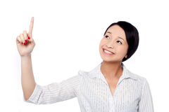 Smiling pretty girl looking and pointing upwards Stock Photos