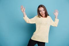 Smiling pretty girl making funny faces over blue background Stock Photos