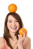 Smiling pretty girl with orange on head fnd hand Royalty Free Stock Images