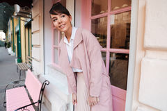 Smiling pretty girl in pink coat standing outside cafe Royalty Free Stock Photo