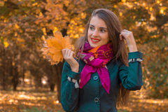 Smiling pretty girl in pink scarf stands in the Park clings to the hair while the other hand holds the leaves Royalty Free Stock Photos