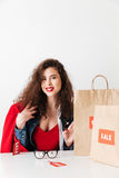 Smiling pretty girl shopaholic sitting with paper shopping bags Royalty Free Stock Image