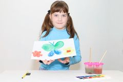 Smiling pretty girl shows picture with butterfly