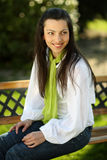 Smiling pretty girl sitting on a bench. Smiling pretty girl with green scarf sitting on a bench in the park stock photos