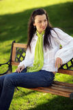 Smiling pretty girl sitting on a bench. Smiling pretty girl with green scarf sitting on a bench in the park royalty free stock photography
