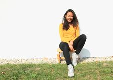 Smiling pretty girl sitting on wooden grinder. Portrait of pretty Papuan girl with curly hair dressed in yellow t-shirt, black pants and white shoes - smiling Stock Photos