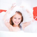 Smiling pretty girl is taking a bath. Small pretty girl is taking a bath with a foam Royalty Free Stock Photos