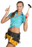 Smiling pretty girl with tool belt holding hammer Royalty Free Stock Photography