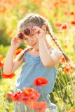 Little girl posing in a poppies Royalty Free Stock Photos