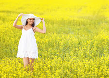 Smiling pretty girl in white in blooming field Stock Photography
