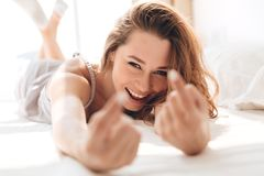 Smiling pretty lady lies in bed indoors calls you. Image of young smiling pretty lady lies in bed indoors calls you. Looking at camera Stock Images