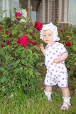Smiling pretty little child girl with flower in park Stock Photo