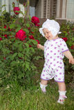 Smiling pretty little child girl with flower rose. In park Stock Photos