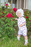 Smiling pretty little child girl with flower rose. In park Stock Photography