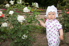 Smiling pretty little child girl with flower rose. In park Royalty Free Stock Photography