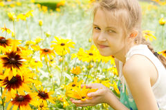 Smiling pretty little girl amongst summer flowers Stock Photo