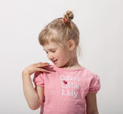 Smiling pretty little girl playing with a toy. Neutral background Royalty Free Stock Photo