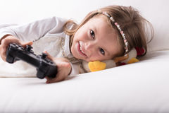 Smiling pretty little girl playing video games Royalty Free Stock Images