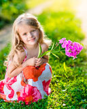 Smiling pretty little girl squatting and holding purple flower Stock Photo