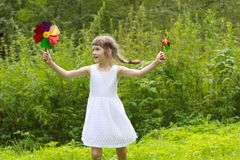 Smiling pretty little girl with two windmills spins. In summer green forest Stock Image
