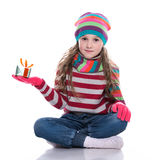 Smiling pretty little girl wearing coloful knitted scarf, hat and gloves, holding christmas gift isolated on white background. Royalty Free Stock Photography