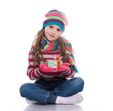 Smiling pretty little girl wearing coloful knitted scarf, hat and gloves, holding christmas gift isolated on white background. Royalty Free Stock Images