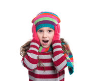Smiling pretty little girl wearing colorful knitted scarf, hat and gloves isolated on white background. Winter clothes. Royalty Free Stock Photos