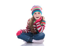 Smiling pretty little girl wearing colorful knitted scarf, hat and gloves isolated on white background. Winter clothes. Stock Image